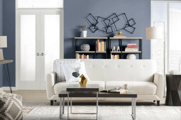 Blue gray paint color in living room with white area rug and white sofa