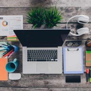 desktop with computer clipboard coffee headphones newsletter